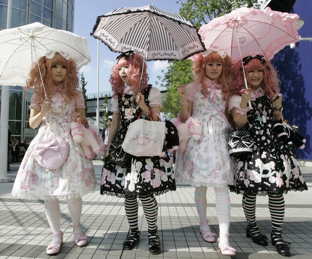"""Japanese women dressed in Lolita fashion walk in front of the venue of """"Individual Fashion Expo. IV"""" fashion event in Tokyo"""